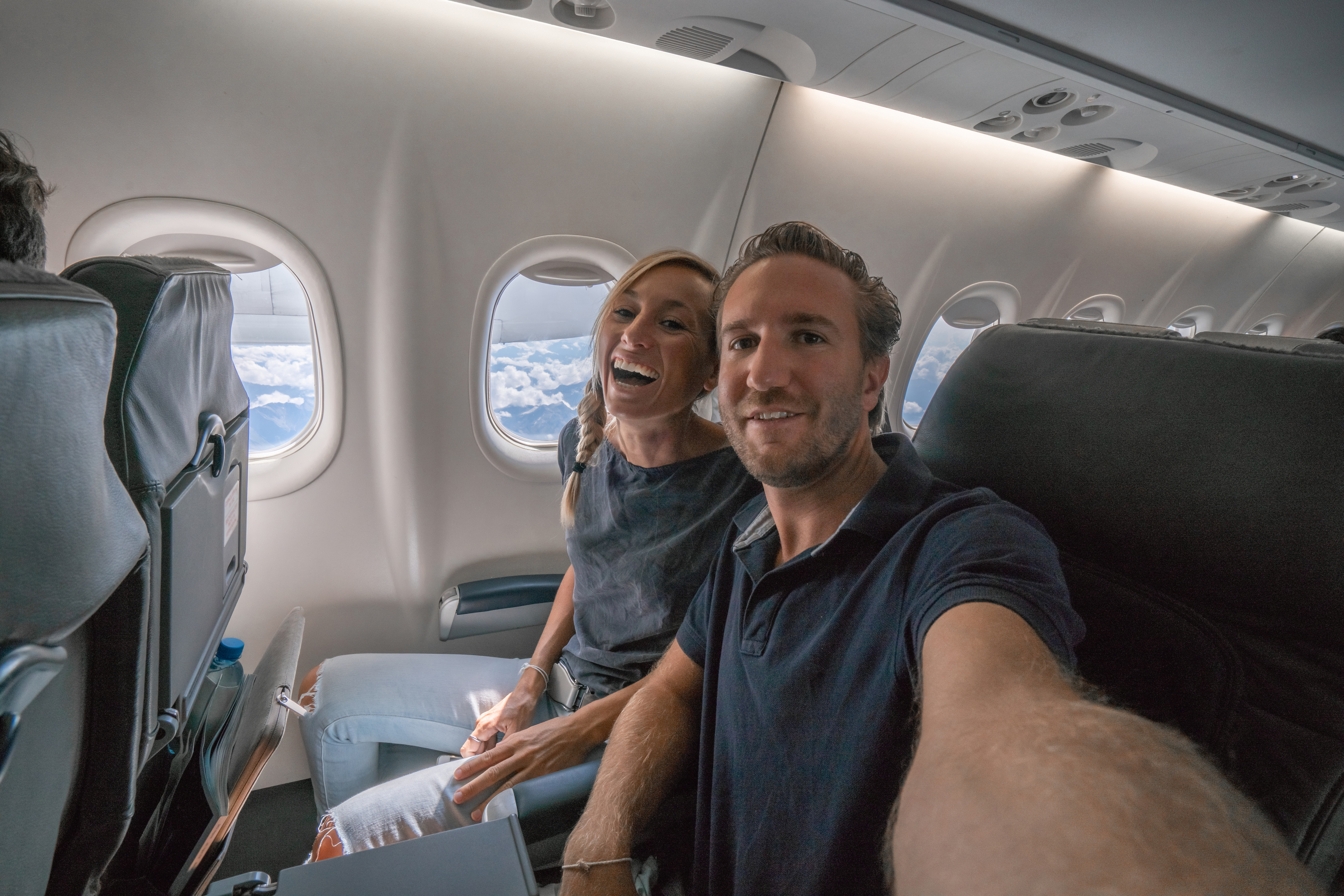 couple taking a selfie from plane seat