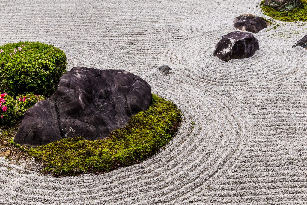 Rocks and moss surrounded by raked sand in a rock garden.
