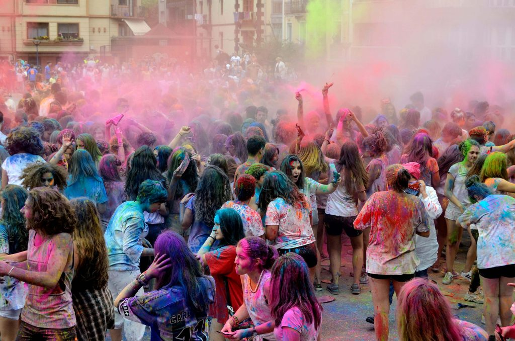 Celebrants of Holi fling colors on each other