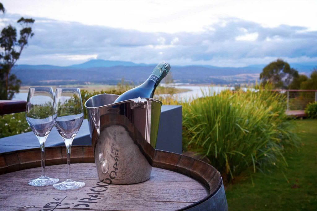 Wine glasses and view of the landscape of Tasmanian winery, Tamar Ridge.